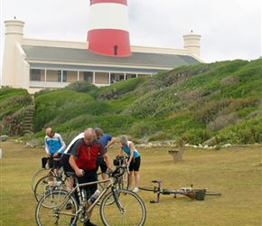 Steve remantling his bike under the shadow of the lighthouse at Cape Aguilas