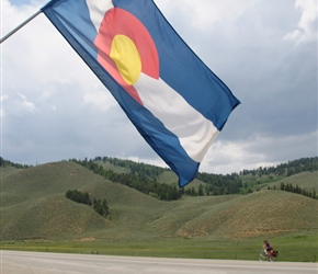 The colors in Colorado's flag represent the environmental features of the state. White symbolizes the snow on her mountains, gold acknowledges the abundant Colorado sunshine, red represents Colorado's red soil, and blue is a symbol of her clear blue
