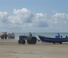 Pulling boat out of the sea at Gouville sur Mer