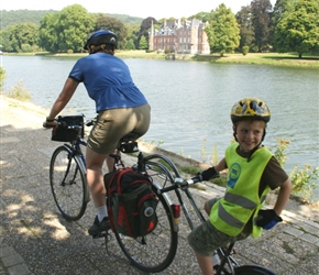 Siobhan and Jacob cycle pass John Chateau on the River Meuse