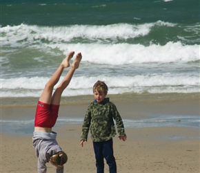 Jacob checks out Alice's handstand on Anse Beach